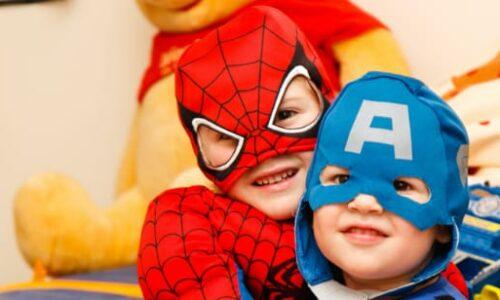 Two children dressed in superhero costumes