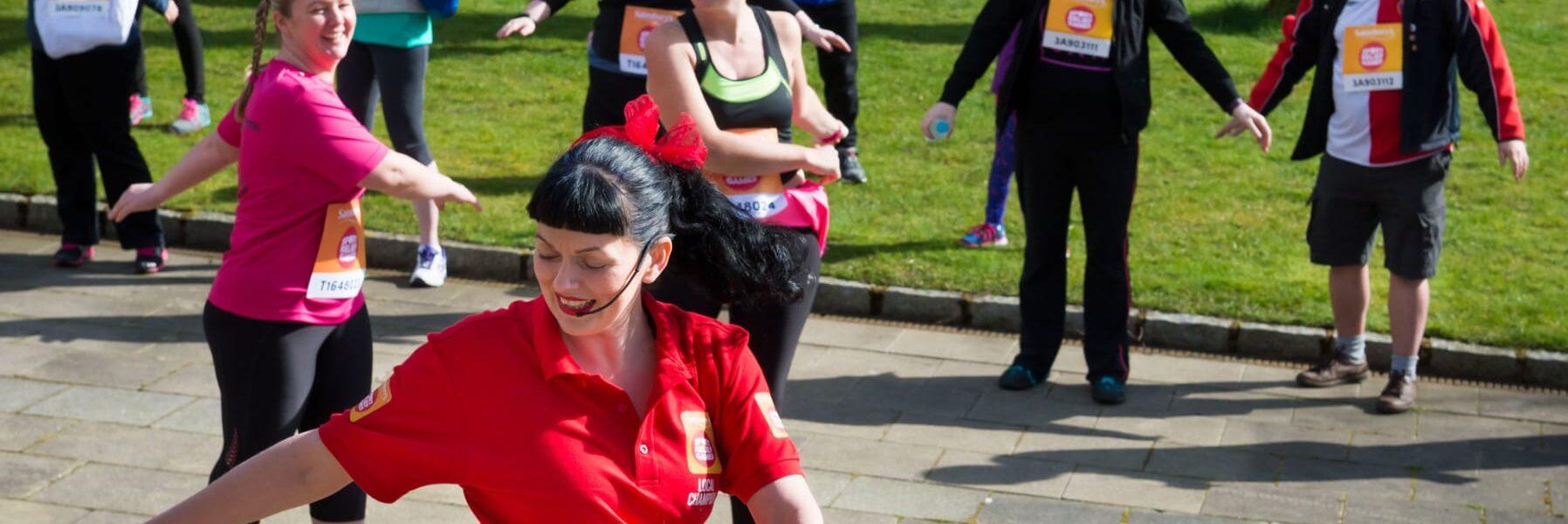 A fitness instructor leads an outdoors aerobics class