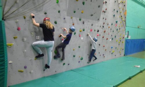 Three people on a climbing wall