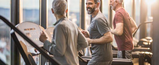 Three active seniors exercising on treadmill
