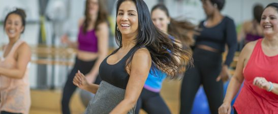 A multi-ethnic group of adult women are dancing in a fitness studio. They are wearing athletic clothes.