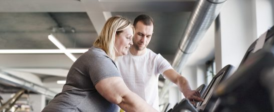 Lady with Personal trainer running on treadmill in gym.