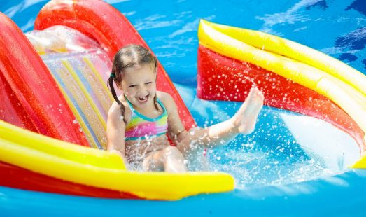 Child on water slide in pool
