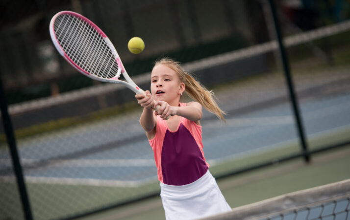 Girl playing tennis and hitting a ball with the racket