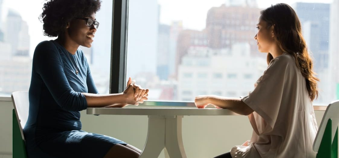 Two women have a conversation while sat around a small table