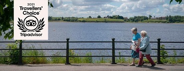 Picture of two people walking lakeside at Hollingworth Lake,. Image shows the Travellers Choice Award 2021 logo to recognise Hollingworth Lake being awarded a Tripadvisor Travellers Choice Award 2021