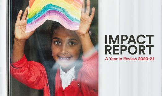image of young girl holding up a rainbow picture against a window. Image used on the front cover of the Impact Report 202-21
